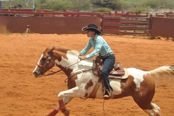 woman in cowboy hat on pinto horse barrel racing rodeo kauai