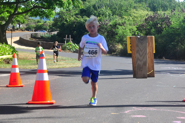 young boy finishing race. Photo by Ray Gordon