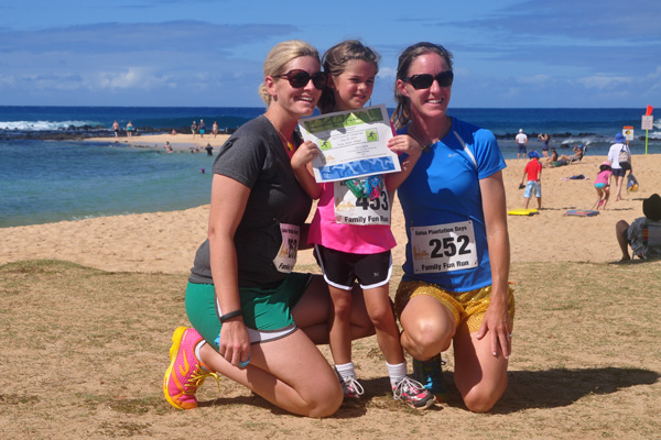 Young girl race finisher with family
