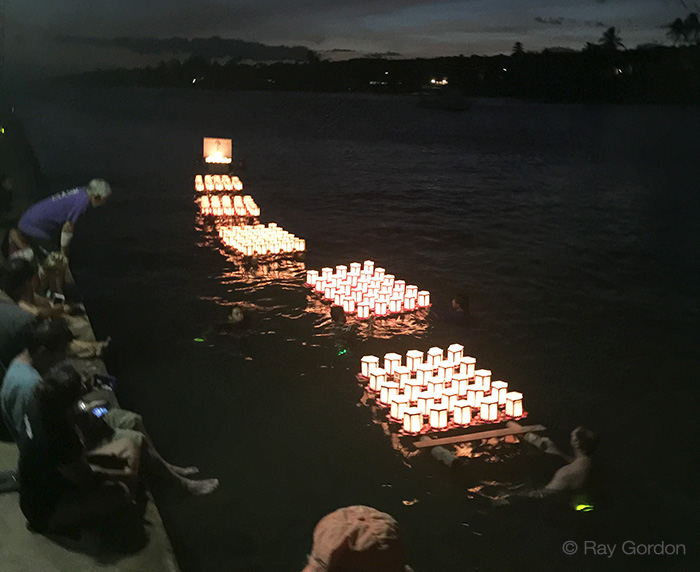 The swimmers continue to wire together incoming rafts of lanterns - photo by Ray Gordon